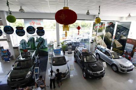 Customers look at new cars at an auto dealership in Shanghai August 5, 2010. REUTERS/Aly Song/Files