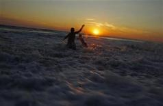 <p>Ricky Ibanez (L) and Eddie Conley play in the surf as the sun sets on Moshup Beach in Aquinnah, Massachusetts on Martha's Vineyard, August 28, 2010. REUTERS/Jim Young</p>