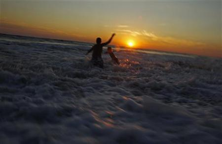 Ricky Ibanez (L) and Eddie Conley play in the surf as the sun sets on Moshup Beach in Aquinnah, Massachusetts on Martha's Vineyard, August 28, 2010. REUTERS/Jim Young