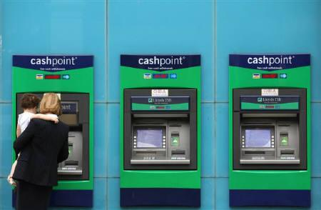 A woman uses an ATM machine in Chelsea, central London, August 4, 2010. REUTERS/Andrew Winning/Files
