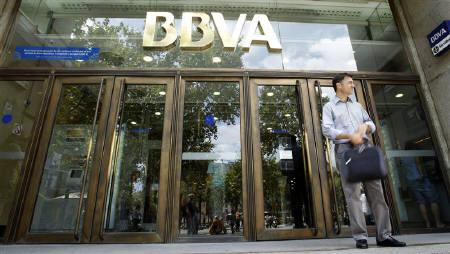 A man waits in front of a BBVA bank branch in central Barcelona July 23, 2010. REUTERS/Albert Gea/Files