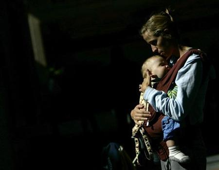 A nursing mother holds her son in front of the Delta airlines counter during a protest at Fort Lauderdale airport, Florida November 21, 2006. REUTERS/Carlos Barria