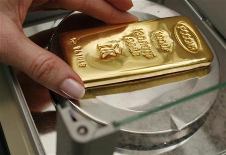 An employee weighs gold ingots in a room for final weighing and packaging at the Krastsvetmet plant in the Siberian city of Krasnoyarsk November 16, 2009. REUTERS/Ilya Naymushin