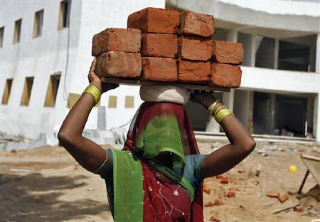 A labourer carries bricks at a residential complex under construction in Ahmedabad September 2, 2010.REUTERS/Amit Dave