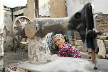 An ethnic Uzbek woman looks through a damaged sewing machine at her house, destroyed during fierce ethnic clashes, in the city of Osh August 21, 2010.