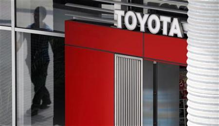 A man is reflected in a window as he walks past a Toyota Motor Corp showroom in Tokyo June 24, 2010. REUTERS/Yuriko Nakao