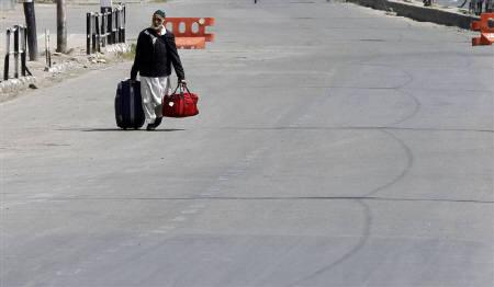 A man walks at a deserted road during a curfew in Srinagar September 17, 2010. REUTERS/Danish Ismail