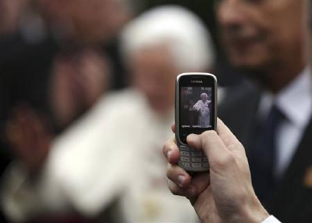 A bishop takes a photograph of Pope Benedict XVI with a mobile phone in the Chapel at Oscott College seminary in Birmingham, central England  September 19, 2010. REUTERS/Simon Dawson/Pool