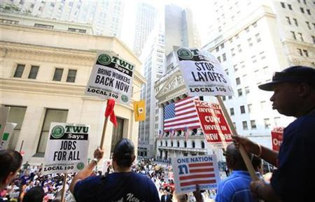 Protesters hold signs aloft during a rally for unemployed people in front of the New York Stock Exchange in New York September 1, 2010. REUTERS/Lucas Jackson