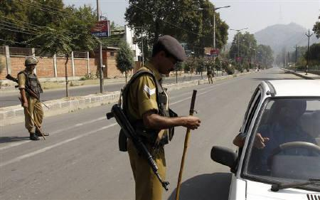 A police officer checks the document of a driver during a curfew in Srinagar September 20, 2010. REUTERS/Danish Ismail