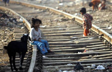 A girl sits on a rail track in a slum in Mumbai February 23, 2009.  About one billion slum dwellers in developing countries are vulnerable to disasters because they live in congested and poorly built houses without emergency services, the Red Cross said in a report released on Tuesday.REUTERS/Arko Datta/Files