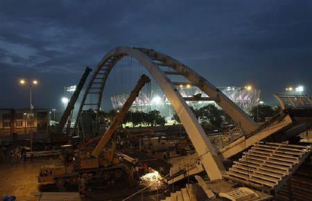 Cranes work at the site of a pedestrian bridge that collapsed outside the Jawaharlal Nehru Stadium in New Delhi September 21, 2010. REUTERS/Adnan Abidi