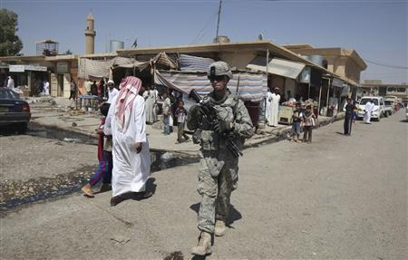 A U.S. soldier on patrol walks past Iraqi residents in Mosul, 390 km (240 miles) north of Baghdad, September 5, 2010. REUTERS/Saad Shalash