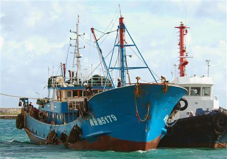 A Chinese fishing boat (blue), flanked by a Japan Coast Guard vessel, is moored at Ishigaki port on the southern Japanese island of Ishigaki, September 8, 2010. REUTERS/Kyodo