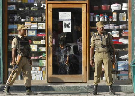 Policemen stand guard as Kashmiri people shop inside a shop during a relaxation in curfew in Srinagar September 26, 2010. REUTERS/Fayaz Kabli