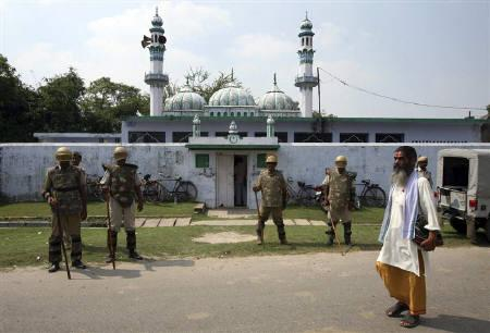 A Hindu priest walks past paramilitary troopers guarding a mosque as Muslims offer Friday prayers in the northern Indian town of Ayodhya October 1, 2010. REUTERS/Mukesh Gupta