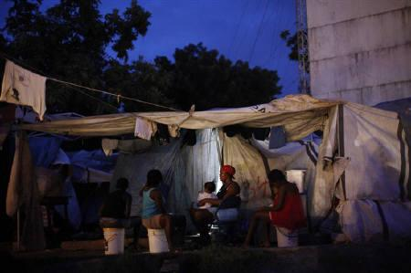 Earthquake survivors rest in their self-constructed improvised tent in Port-au-Prince October 1, 2010.  REUTERS/Eduardo Munoz