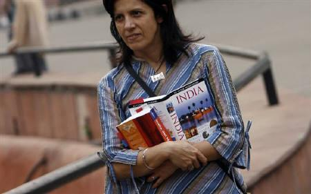 A foriegn tourist holds tourist guide books as she visits the Red Fort in the old quarters of Delhi November 12, 2008. REUTERS/Adnan Abidi/Files
