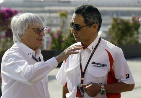Formula One supremo Bernie Eclestone (L) talks to Hiroshi Yasukawa, director of Bridgestone Motorsport Division, before the first practice session ahead of European F1 Grand Prix in Valencia June 25, 2010. REUTERS/Heino Kalis/Files