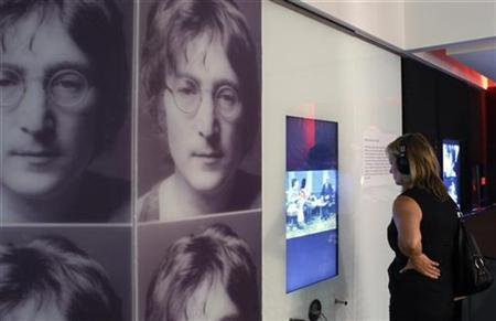A woman watches a video at the ''John Lennon, Songwriter'' exhibit during a press preview at the Grammy Museum in Los Angeles October 1, 2010. REUTERS/Fred Prouser
