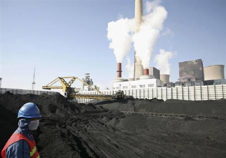 A worker stands at a coal dump site of Daba power plant in Qingtongxia, Ningxia Hui Autonomous Region October 8, 2010. REUTERS/Tom Yz
