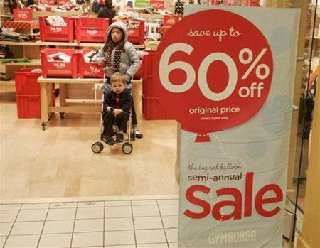 Two children stand near a 60 percent off sale sign at a Gymboree children's clothing store as shoppers buy gifts on Christmas Eve at the Beverly Center shopping mall in Los Angeles, California December 24, 2008. REUTERS/Fred Prouser