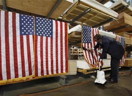 House Republican staff member Ben Howard steam irons American flags before House leaders hold a roundtable discussion on ''A New Governing Agenda'' for Congress at the Tart Lumber Company in Sterling, Virginia, September 23, 2010. REUTERS/Larry Downing
