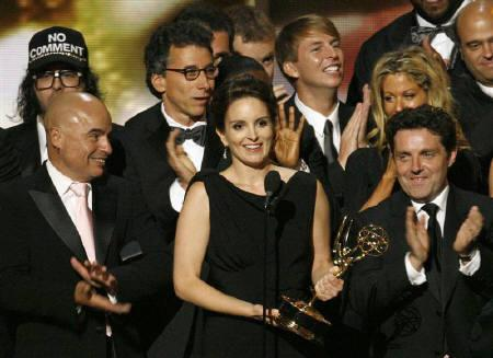 Tina Fey (C) stands with the cast and crew of ''30 Rock'' as they accept the award for best comedy series at the 61st annual Primetime Emmy Awards in Los Angeles, California September 20, 2009. REUTERS/Mario Anzuoni/Files