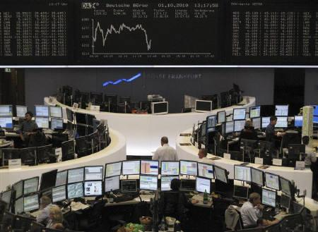 Traders are pictured at their desks in front of the DAX board at the Frankfurt stock exchange October 1, 2010. REUTERS/Remote/Kirill Iordansky/Files