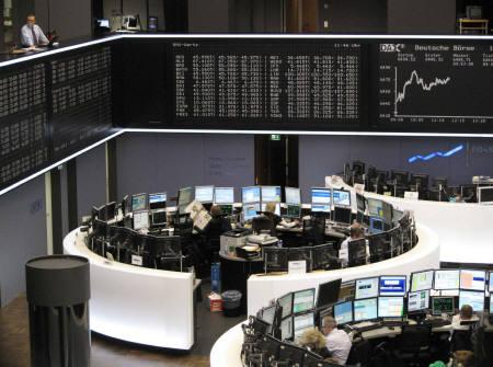 Traders are pictured at their desks in front of the DAX board at the Frankfurt stock exchange October 14, 2010. REUTERS/Remote/Pawel Kopczynski