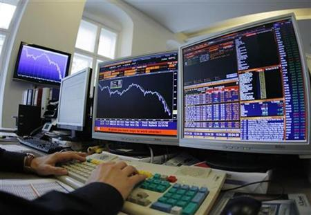 An index manager at the Vienna Stock Exchange sits in front of screens displaying a one-year graph of the ATX index in Vienna October 29, 2008. REUTERS/Heinz-Peter Bader