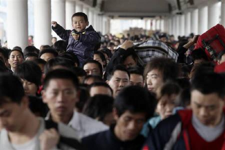 Passengers rush to board a train at the Guangzhou railway station, Guangdong province February 19, 2010. REUTERS/Joe Tan/Files