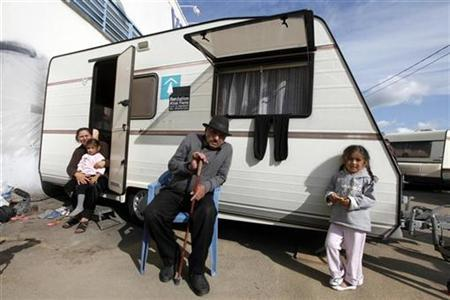 A Roma family stand in front a caravan near Paris, September 16, 2010. REUTERS/Jacky Naegelen
