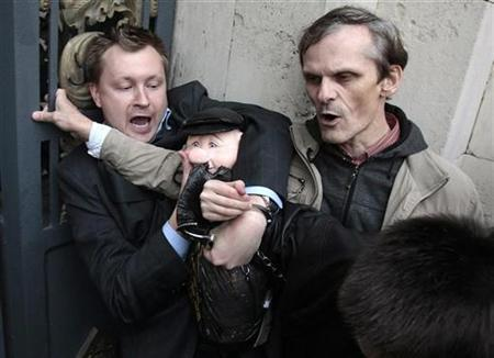 Police detain a gay rights activist holding a puppet of Moscow mayor Yuri Luzhkov during an unsanctioned protest in Moscow September 21, 2010. REUTERS/Alexander Natruskin