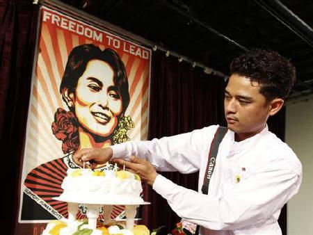A Burmese activist lights candles on a cake in front of a portrait of Myanmar's detained pro-democracy leader Aung San Suu Kyi during an event celebrating her birthday in Bucheon, west of Seoul June 20, 2010. REUTERS/Jo Yong-Hak/Files