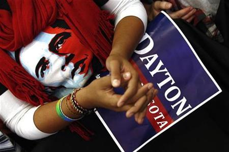 A woman wearing an Obama shirt listens as U.S. President Barack Obama speaks in support of gubernatorial candidate Mark Dayton at a campaign rally in Minneapolis, Minnesota October 23, 2010. REUTERS/Kevin Lamarque