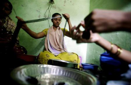 A customer of a micro finance institution strings beads into necklaces at a workshop in a slum area in Mumbai February 17, 2007.    REUTERS/Prashanth Vishwanathan/Files