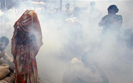 Women cover their faces as a health worker fumigates a slum to prevent malaria in Mumbai December 15, 2009. REUTERS/Arko Datta