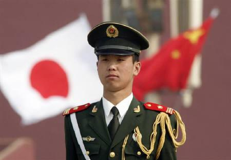 A paramilitary policeman stands guard in front of a Chinese and a Japanese flag at Tiananmen Square in Beijing April 29, 2009. REUTERS/Christina Hu/Files