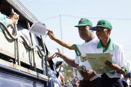Members of the Union Solidarity and Development Party (USDP) hand out flyers during a campaign rally near a market outside of Yangon October 30, 2010. REUTERS/Soe Zeya Tun