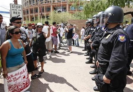 Protesters (L), against SB 1070, yell at police officers outside the Phoenix courthouse in Phoenix, Arizona, July 29, 2010. REUTERS/Rick Scuteri