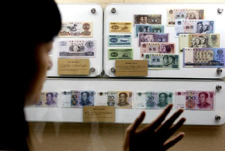A Chinese museum guide explains different sets of yuan notes for visitors at the Shanghai Bank Museum July 22, 2005. REUTERS/Ming Ming/Files