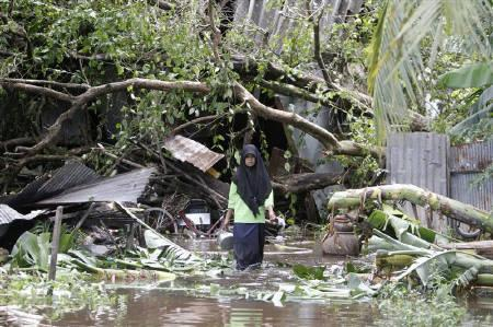 A Thai girl carries belongings out of her flooded home in the southern province of Pattani November 2, 2010. Transport and communications were severed and tourists stranded on Wednesday after southern Thailand's worst flash floods in a decade forced flight cancellations and left a bustling city in deep water. REUTERS/Surapan Boonthanom/Files