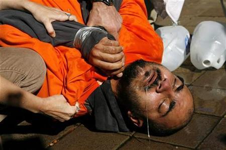 Demonstrator Maboud Ebrahimzadeh lies on the pavement after his ordeal in a simulation of waterboarding outside the Justice Department in Washington November 5, 2007. REUTERS/Kevin Lamarque