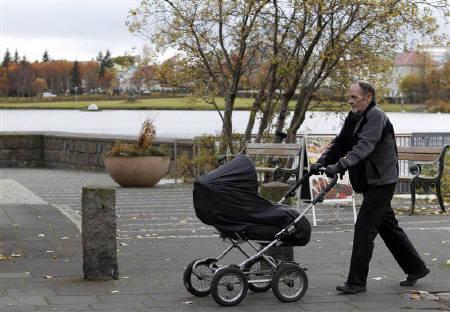 A man pushes a baby pram in a park in Reykjavik October 12, 2010. REUTERS/Chris Helgren/Files