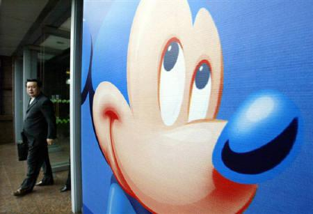 A Chinese shopper stands near Disney's Mickey Mouse poster at ashopping mall in Shanghai November 14, 2003. REUTERS/Claro Cortes/Files