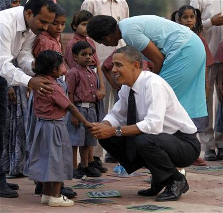 U.S. President Barack Obama and first lady Michelle Obama greet the children of workers who restore New Delhi's historical buildings, as they tour Humayun's tomb in New Delhi November 7, 2010. REUTERS/Jason Reed