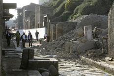 <p>Pessoas ao lado das ruínas de uma casa desmoronada, antigamente usada por gladiadores para treinar antes do combate, em Pompéia. 06/11/2010 REUTERS/Ciro De Luca</p>