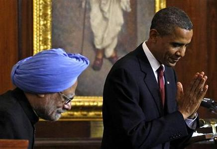 President Barack Obama bows and makes a greeting to the audience beside India's Prime Minister Manmohan Singh after delivering a speech at Parliament House in New Delhi, November 8, 2010. REUTERS/Jim Young