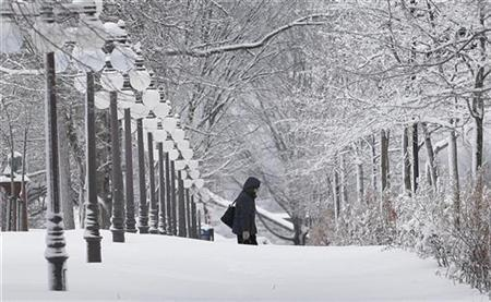 A woman walks in the streets of the Old Quebec during a snow storm in Quebec City February 25, 2010. REUTERS/Mathieu Belanger